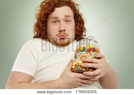 Close Up Shot Of Sad Chubby Caucasian Man With Curly Ginger Hair Holding Jar Of Marmalades, Feeling