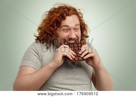 Plump Funny Redhead Young Caucasian Male With Curly Hair Biting Large Of Chocolate With Pleased Joyf