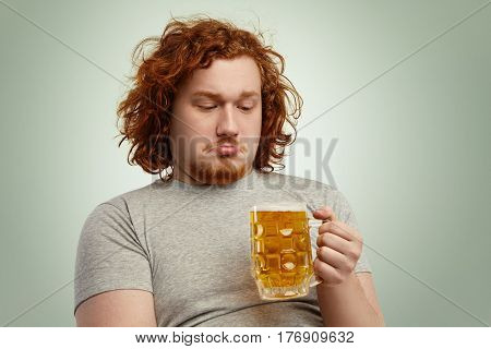 Close Up Shot Of Indecisive Male With Ginger Hair Holding Glass Of Beer In His Hands, Looking At Col