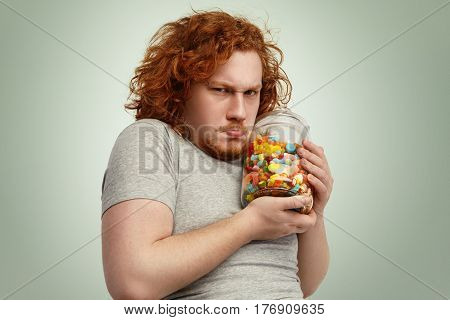 Obese Chubby European Man With Ginger Curly Hair Holding Jar Of Sweets Tight, Having Greedy Look, Fr