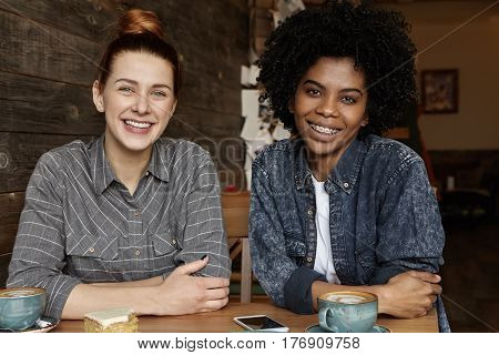 Two Happy Lesbians Having Coffee, Sitting At Table At Cozy Restaurant. Stylish African Woman Relaxin