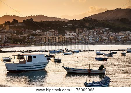 Boats In Marina Of Giardini Naxos Town On Sunset