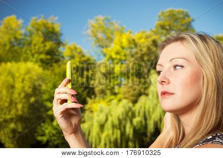 Technology photography outdoor relaxation concept. Woman sitting in park relaxing using mobile phone and taking pictures of nature spending her leisure time outside