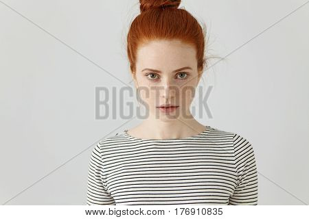 Portrait Of Gorgeous Young Female With Clean Healthy Skin With Freckles And Hair Knot Staring At Cam
