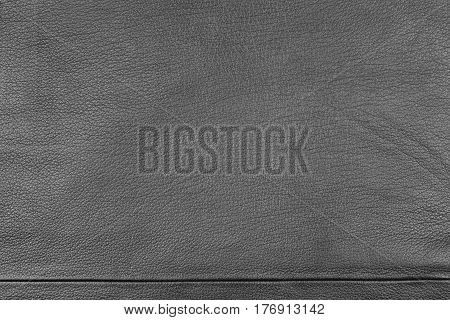 Closeup texture of natural or artificial leather and seam. View from above