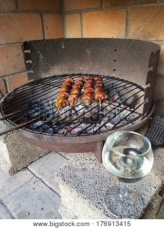 Barbequing kebabs over smoldering charcoal on old fashioned style barbeque grill on concrete blocks in brick surround and wine glass