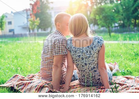 A happy young modern couple in a park on plaid sits, declaration of love, natural heart-to-heart conversation, happy family, a teenage life style, a new family