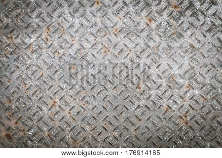 Old metal floor plate with diamond pattern and rusty background texture.