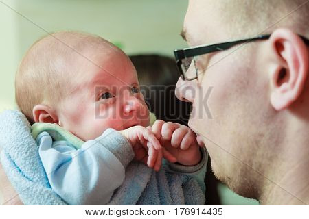 Family fatherhood concept. Daddy holding his little newborn baby in blanket close up.