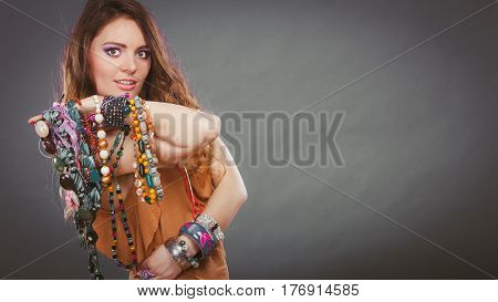 Pretty young woman wearing bracelets and rings holding many plentiful of precious jewelry necklaces beads. Gorgeous fashion girl.