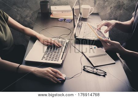 Coworkers working on the same desk they are using a laptop with tablet Start up business concept Vintage tone