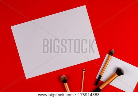 Make up brushes with white blank paper on red background. Top view. Flat lay. Copy space for text