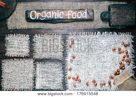 Rustic style template for food and drink industry. Burlap frames on dark wood background with nuts and spices. Wooden cutting boards and signboard with text 'Organic food' as title bar