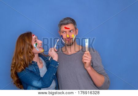 coloring couple holding brushes smiling