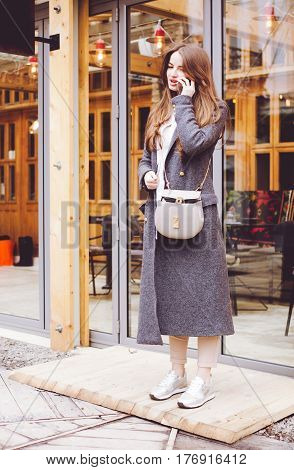 Beautiful fashionable girl in gray coat trousers and sneakers speaks on the smartphone leaving the restaurant. Outdoor. Fashion and beauty.