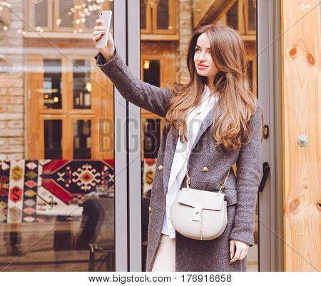 Beautiful fashionable girl in gray coat trousers and sneakers with a trendy handbag makes selfie smartphone near the exit from the restaurant. Outdoor. Fashion and beauty.