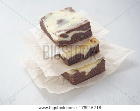 Pile of three marble chocolate brownies. Homemade dessert upon parchment. Square pieces of brownie cheesecake. Selective focus on the front.