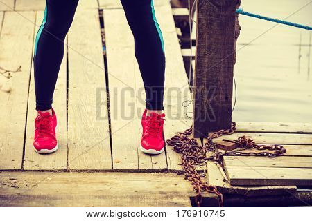 Slim Fit Legs Wearing Red Sport Shoes On Wooden Pier