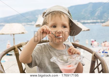 Toddler eating ice cream in a cafe on the beach against the backdrop of the sea and mountains