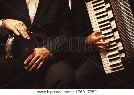 Two Musicians On Their Instruments