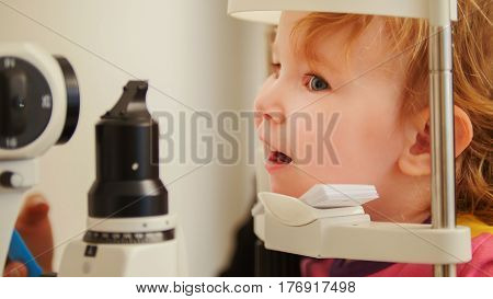 Little girl in ophthalmological clinic checks eyesight, telephoto