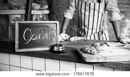 African Man with Open Sign in Bakery Shop