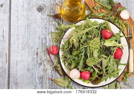 Fresh green salad with radish. Herbs such as chard, lettuce, beet leaves on a white metal plate on a cutting board, next to a glass jug with olive oil.