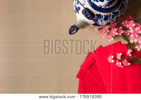 Top view of chinese plum blossoms with red packets and teapot on the table Chinese new year concept Free space for text