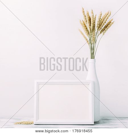 White horizontal empty frame with wheat bouquet in white vase on table. Pure minimalistic background with copyspace