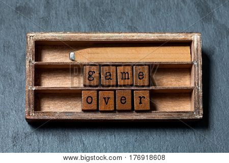 Game over quote and failure concept. Vintage box, wooden cubes with old style letters, retro style pencil. Gray stone textured background. macro, up view, soft focus