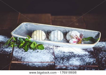 Mochi dessert in plate with flower on wood table