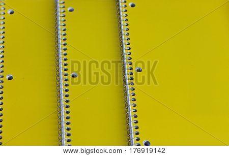 Three Yellow Spiral Notebooks Arranged on a Desk