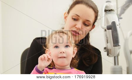 Mother and doughter in ophthalmologist room, horizontal