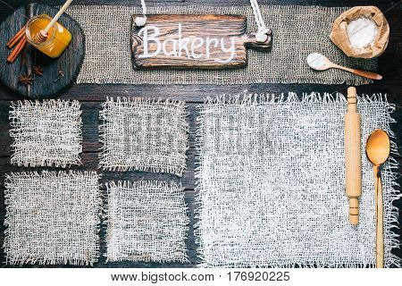 Rustic style template for food and drink industry. Burlap frames on dark wood background with flour pack, roller and honey. Wooden cutting boards and signboard with text 'Bakery' as title bar