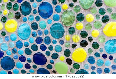 Blue and Yellow Glass Beads in Concrete wall