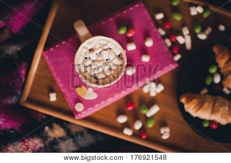 Cup of coffee with marshmallow staying gin pink book black plate with croissant and sweets on wooden tray. Top view. Selective focus.