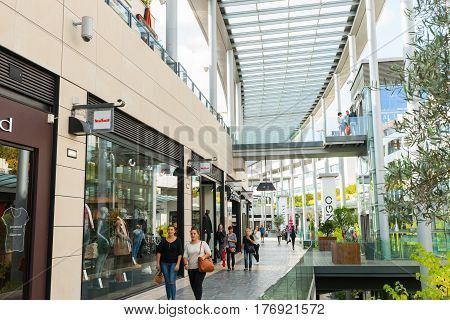 Beziers France - October 6, 2016; Architecture of modern shopping center with customers walking through