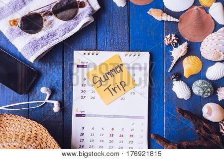 Top view of calendar with accessories for summer trip and seashells on blue painted wood plank background.