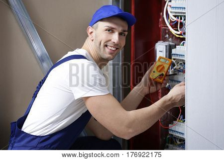 Electrician measuring voltage in distribution board