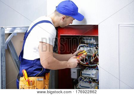 Electrician connecting wires in distribution board
