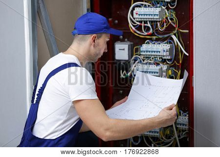 Electrician with wiring diagram checking connections in distribution board