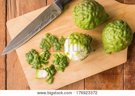 Sliced skin bergamot or kaffir lime with knife on wooden table background.