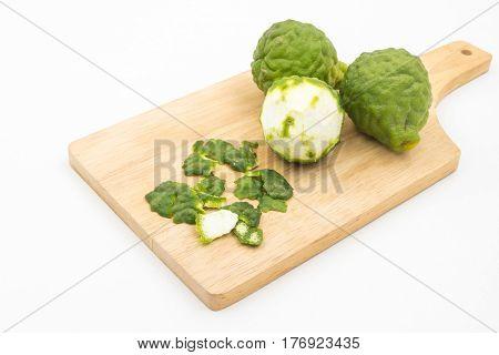 Sliced skin bergamot or kaffir lime on wooden tray over white background.