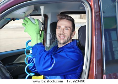 Handsome male cleaner removing dirt from car salon