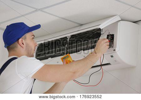 Electrician measuring voltage in air conditioner
