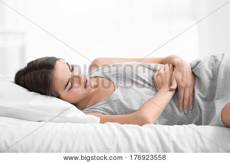 Young woman suffering from abdominal pain while lying on bed at home. Gynecology concept