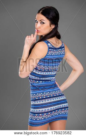 Young beautiful brunette woman has put forefinger to lips as sign of silence, studio wall background
