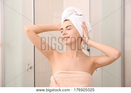 Beautiful young woman with towel on head in shower