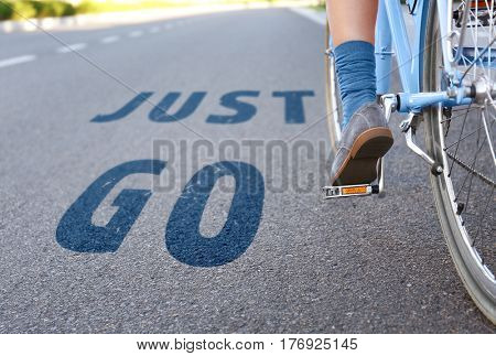 Woman riding on bicycle and text JUST GO on road background