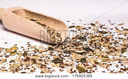 Sesame seeds, pumpkin seeds, sunflower seeds, chia seeds, flax seeds, poppy seeds and a wooden spoon